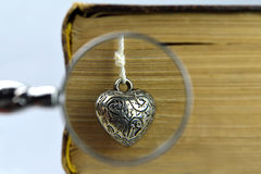 Livre, coeur argenté et loupe Image stock