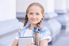 Livre d'étreinte d'écolier de la jeunesse dans l'uniforme occasionnel Entrez à l'école photo stock