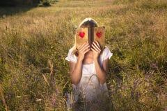 Livre d'amour de lecture de femme dehors Image stock