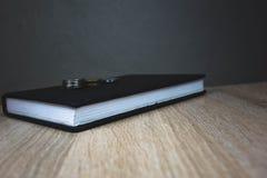 Livre dans le mensonge ferme de couverture sur une table en bois images stock