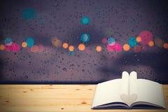 Livre de coeur sur le fond en bois, dans la nuit pluvieuse Image libre de droits