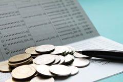 Livre de comptes d'économie ou relevé de compte financier et pièces de monnaie sur la table de bureau photographie stock