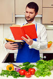 Livre de cuisine beau du relevé de jeune homme attentivement Image stock