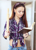 Livre de cuisine de lecture de jeune femme Photographie stock libre de droits