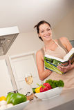 Livre de cuisine du relevé de jeune femme dans la cuisine Photo stock