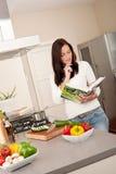 Livre de cuisine du relevé de jeune femme dans la cuisine Image stock