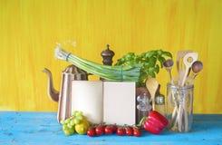 Livre de cuisine, légumes, ustensiles de cuisine Photos stock