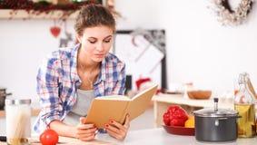 Livre de cuisine de lecture de jeune femme dans la cuisine, recherchant la recette Image libre de droits