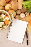 Livre de cuisine ou bloc-notes avec le plat de cocotte en terre et légumes organiques sur le plan de travail de cuisine, l'espace Images libres de droits