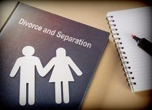 Livre de divorce et de séparation à côté d'un carnet Photos stock