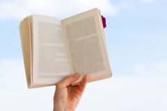 Livre de fixation de main au-dessus de ciel bleu Images libres de droits