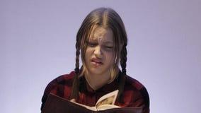 Livre de l'adolescence irrité de lecture de fille concernant quelque chose dégoûtant 4k UHD clips vidéos