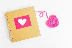 Livre de l'amour avec le coeur rose de crochet sur le fond blanc Photo libre de droits