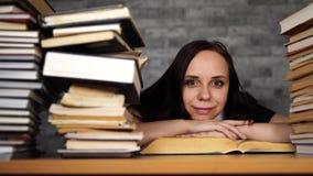 Livre de lecture étant ennuyeux d'étudiante à la bibliothèque avec beaucoup de livres à l'université clips vidéos