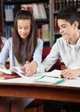 Livre de lecture adolescent de couples ensemble dans la bibliothèque Photos stock