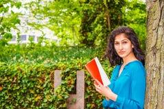 Livre de lecture américain d'étudiant universitaire d'Indien est dehors dans nouveau images libres de droits