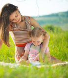 Livre de lecture assez jeune de mère à sa petite fille photographie stock libre de droits
