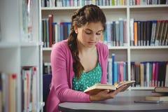 Livre de lecture attentif d'écolière dans la bibliothèque Image libre de droits