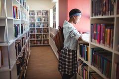 Livre de lecture attentif d'écolière dans la bibliothèque Image stock
