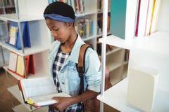 Livre de lecture attentif d'écolière dans la bibliothèque Photographie stock libre de droits