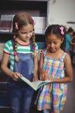 Livre de lecture attentif d'écolières dans la bibliothèque Photos stock