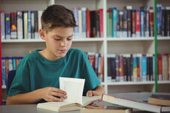 Livre de lecture attentif d'écolier dans la bibliothèque Images stock