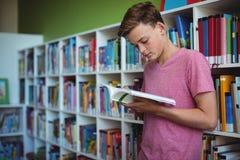 Livre de lecture attentif d'écolier dans la bibliothèque Photos stock