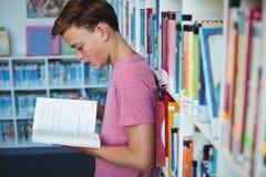 Livre de lecture attentif d'écolier dans la bibliothèque Image libre de droits
