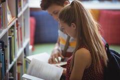 Livre de lecture attentif de camarades de classe dans la bibliothèque Photo stock