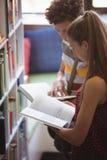 Livre de lecture attentif de camarades de classe dans la bibliothèque Images stock