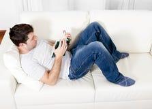 Livre de lecture attrayant d'homme ou étude sur le divan Photos stock