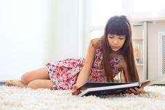 Livre de lecture avec du charme de petite fille Photo stock