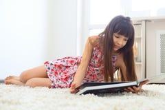 Livre de lecture avec du charme de petite fille Images stock