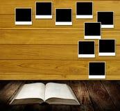 Livre de lecture avec le poteau de cadres de photo sur le mur en bois Photographie stock libre de droits
