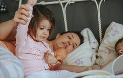 Livre de lecture de bébé avec la famille dans le lit images stock