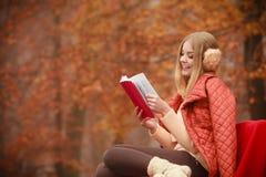 Livre de lecture blond de fille dans le paysage d'automne photo stock