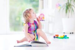 Livre de lecture bouclé drôle de fille d'enfant en bas âge se reposant sur le plancher photos libres de droits
