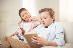 Livre de lecture caucasien de soeur et de frère ensemble à la maison Photographie stock
