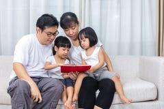 Livre de lecture chinois asiatique de parents et de filles sur le sofa Images libres de droits