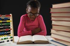Livre de lecture d'écolière sur le fond noir Photographie stock libre de droits