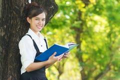 Livre de lecture d'étudiant en parc, se tenant sous un arbre OU de détente Image libre de droits