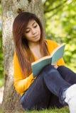 Livre de lecture d'étudiante contre le tronc d'arbre en parc Photographie stock libre de droits