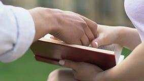 Livre de lecture d'étudiante dehors, ami tenant tendrement sa main clips vidéos