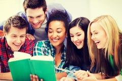 Livre de lecture d'étudiants à l'école Photos stock