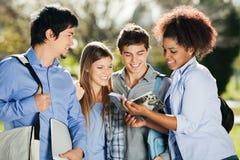 Livre de lecture d'étudiants ensemble dans le campus Photos libres de droits
