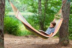 Livre de lecture d'enfant dans l'hamac photos stock