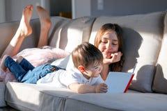 Livre de lecture d'enfants de mêmes parents ensemble sur le divan avec des pieds  Lumi?re dure Soeur et son de petit frère de dép photographie stock libre de droits