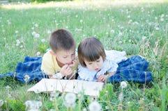 Livre de lecture d'enfants se trouvant sur l'estomac extérieur parmi le pissenlit en parc, enfants mignons éducation et développe Photographie stock libre de droits