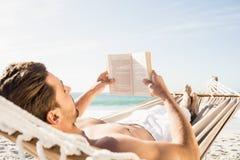 Livre de lecture d'homme dans l'hamac Photos stock