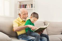 Livre de lecture d'homme supérieur pour son petit-enfant Image stock